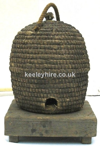 Straw bee hive basket on low wood table