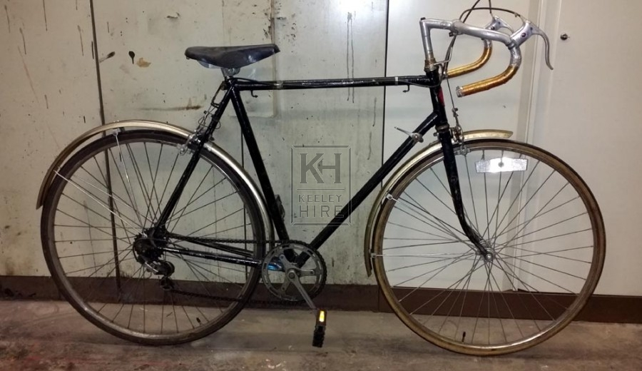 Black racing bicycle with gold mudguards